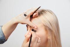 Visagiste med en borste i en hand som s?tter makeup p? ?gonen av modellen, den annan handen, drar huden av ?gonlocket med guld royaltyfri fotografi