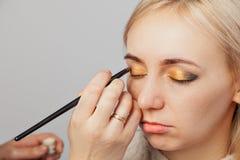 Visagiste med en borste i en hand som s?tter makeup p? ?gonen av modellen, den annan handen, drar huden av ?gonlocket med guld arkivbild