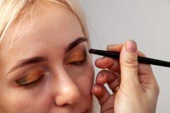 Visagiste met een borstel in één hand die make-up op de ogen van het model zetten, de andere hand trekt de huid van het ooglid me stock foto