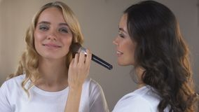 Visagiste putting evening make up on clients face, happy woman ready for party stock footage