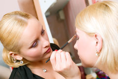 Visagiste.putting on models eye make up Stock Images