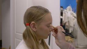Visagiste que aplica el eyehadow en el párpado del modelo del maquillaje en estudio del maquillaje metrajes