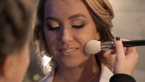 Visagiste que hace el maquillaje para la novia en estudio de la belleza almacen de metraje de vídeo