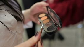 Visagiste que sostiene una paleta de sombreadores de ojos disponible almacen de metraje de vídeo