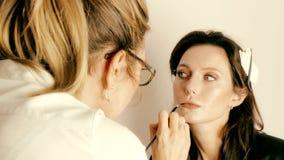 Visagiste som applicerar smink på närbild för framsida för brunettmodell` s lager videofilmer