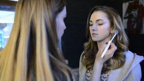 Visagiste utgör för modell i skönhetstudio lager videofilmer