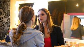 Visagiste wendet Make-up auf dem blonden Modell an, das bewegungsloses sitzt stock footage