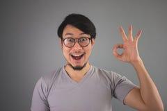 Visar den asiatiska mannen för den roliga framsidan ett ok tecken Royaltyfri Bild