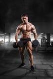 Visar den muskulösa kroppsbyggaremannen för idrottsman nen hans muskler i Arkivfoton