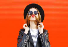 Visar den roliga kvinnan för mode som har gyckel, mustaschhår över färgrikt rött royaltyfria bilder