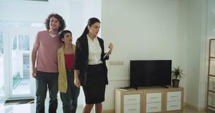 Visar den yrkesmässiga fastighetsmäklaren för den mogna kvinnan att göra ett hus att turnera all den inre moderna designen för en arkivfilmer