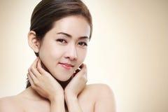 Visar det asiatiska skönhetskottet för kvinnor hennes framsidagoda hälsor på varm guld- bakgrund för färg Royaltyfri Foto