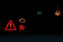 Visar varnande ljus för motorutsläpp på en svart bakgrund Royaltyfri Fotografi