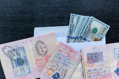 Visas in foreign passports. Visas in foreign passports and an envelope with money are on a black wooden table. Visas in foreign passports Royalty Free Stock Images