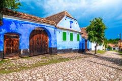 Viscri, Brasov, Румыния: Дом покрашенный синью традиционный от Vis стоковые фото