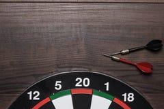 Vise e dois dardos na tabela de madeira marrom Foto de Stock Royalty Free