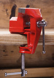 Vise on the workbench. The red grip on the wooden bench Stock Photo