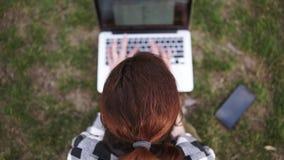 Viser la longueur d'une fille avec une queue de cheveux se repose au sol en parc, imprime sur un ordinateur portable brouillé Le  banque de vidéos