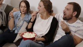 Viser la longueur d'une grande cuvette rouge avec le maïs éclaté Les amis se réunissent ensemble et ont l'amusement au salon clips vidéos