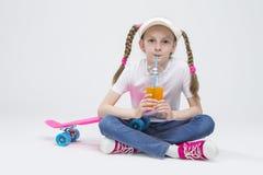 Visera que lleva de la muchacha rubia caucásica que se sienta en piso con la taza de jugo y que bebe a través de la paja Fotografía de archivo