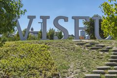 Large metallic letters with the name of city of Viseu, located in urban park of Viseu, background with historical center. Viseu / Portugal - 10/09/2018 : Large royalty free stock image