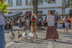 Spectacle view with street theater, medieval fair, actors dressed in typical costumes, walking geese and public watching stock photos