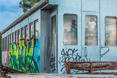 View of a abandoned wagon with graffiti street art and kids reflection on windows glass stock image