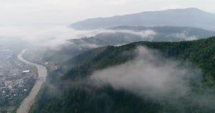 Visión aérea: Bosque brumoso, volando a través de las nubes en la ciudad transcarpática Mizhgirja almacen de video