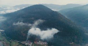 Visión aérea: Bosque brumoso, volando a través de las nubes en la ciudad transcarpática Mizhgirja metrajes