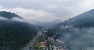 Visión aérea: Bosque brumoso, volando a través de las nubes en la ciudad transcarpática Mizhgirja almacen de metraje de vídeo