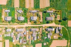 Visión aérea desde la altura del pueblo con las casas y las calles, campos arados, prados en el verano fotografía de archivo
