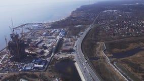 Visión aérea desde la mosca del helicóptero sobre ciudad en el campo de construcción de la costa Río Día asoleado Paisaje urbano metrajes