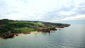 Visión aérea: el vuelo sobre el secadero del  de Ñ de millares aúlla en la playa general con las cáscaras y las rocas cerca de K almacen de metraje de vídeo