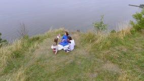 Visión aérea en tres novias que llevan el vestido largo de la moda del verano que se sienta cerca del lago o del río Dos caucásic almacen de metraje de vídeo
