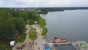 Visión aérea: Lago agradable en el campo Opinión aérea gente en una playa arenosa en el lago Es una visión colorida almacen de metraje de vídeo