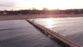 Visión aérea: mar y puesta del sol Puente en el mar Hombre que va a recto almacen de video
