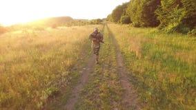 Visión aérea: Militares con el autómata que corre en el bosque almacen de metraje de vídeo