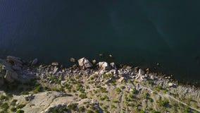 Visión aérea: opinión de la mañana del mar a través de las rocas en la Crimea Hermosa vista de la bahía azul del cabo Kapchik en  almacen de video
