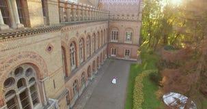 Visión aérea: pares hermosos que caminan en el castillo grande antiguo 4k en puesta del sol almacen de metraje de vídeo