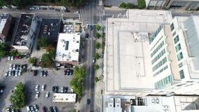 Visión aérea por el abejón de tejados, los estacionamientos y el horizonte de Raleigh, NC almacen de metraje de vídeo