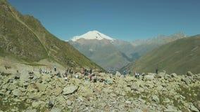 Visión aérea que camina al grupo que se coloca en el borde de la montaña en pico de la nieve del fondo almacen de metraje de vídeo