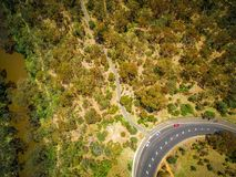 Visión aérea que mira abajo la curva, los árboles, y el parque del camino Imagen de archivo