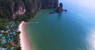 Visión aérea que vuela sobre casas amaizing del hotel hacia las montañas verdes hermosas y la playa arenosa blanca Isla de Krabi almacen de video
