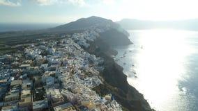 Visión aérea que vuela sobre la ciudad de Oia en Santorini Grecia almacen de metraje de vídeo
