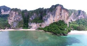Visión aérea que vuela sobre la isla tailandesa hacia las montañas verdes hermosas y la playa arenosa blanca Isla de Krabi, Taila almacen de video