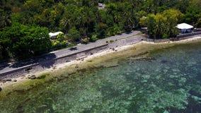 Visión aérea que vuela sobre sorprender de la agua de mar del claro de la playa arenosa del desembarco por playa de la isla de Su metrajes