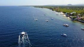 Visión aérea que vuela sobre sorprender de la playa arenosa con los turistas que nadan en la agua de mar clara hermosa de la play almacen de metraje de vídeo