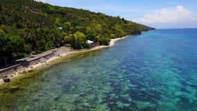 Visión aérea que vuela sobre sorprender de la playa arenosa con los turistas que nadan en la agua de mar clara hermosa de la play almacen de video