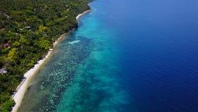 Visión aérea que vuela sobre sorprender de la playa arenosa con los turistas que nadan en la agua de mar clara hermosa de la play metrajes