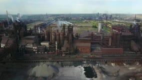 Visión aérea sobre ciudad industrializada con la contaminación de la atmósfera del aire y de agua de río de la planta metalúrgica almacen de metraje de vídeo